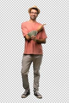 Hombre sosteniendo muchos billetes apuntando al lado para presentar un producto.