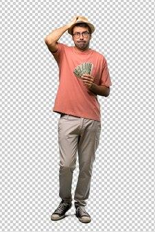 Hombre sosteniendo muchos billetes con una expresión de frustración y falta de comprensión.