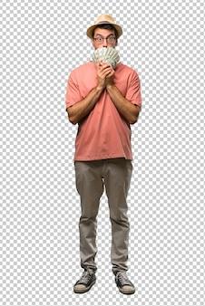 Hombre sosteniendo muchos billetes que cubren la boca con ambas manos por decir algo inapropiado