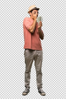 Hombre sosteniendo muchos billetes que cubren los ojos con las manos y mirando a través de los dedos
