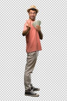 Hombre sosteniendo muchos billetes sonriendo y mostrando el signo de la victoria