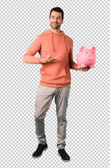 Hombre en una sudadera rosa tomando una alcancía y feliz porque está lleno