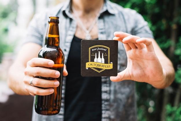 Hombre sujetando la botella de cerveza y posavasos
