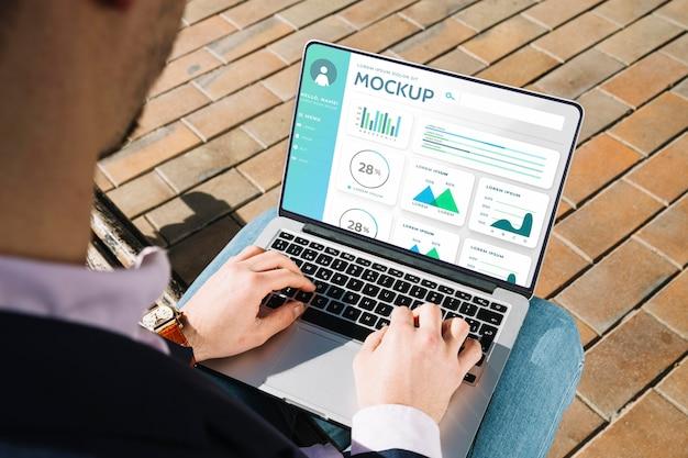 Hombre sujetando una computadora portátil de maqueta para el trabajo