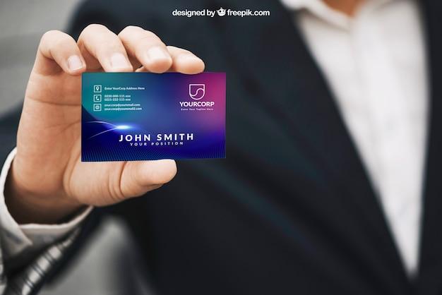 Hombre sujetando mockup de tarjeta de visita