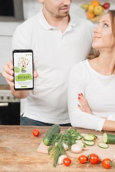 Hombre sujetando el teléfono inteligente en la cocina mientras cocina con mujer