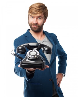Hombre con un teléfono antiguo grande