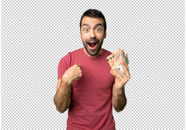 Hombre tomando mucho dinero con expresión facial sorpresa