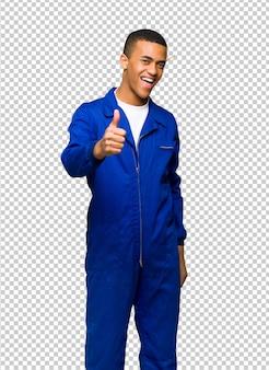 Hombre trabajador afroamericano joven que da un pulgar hacia arriba gesto porque algo bueno ha sucedido