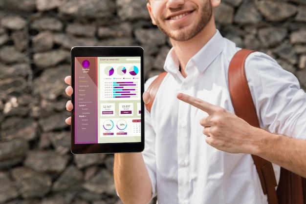Hombre universitario sosteniendo y apuntando a la tableta