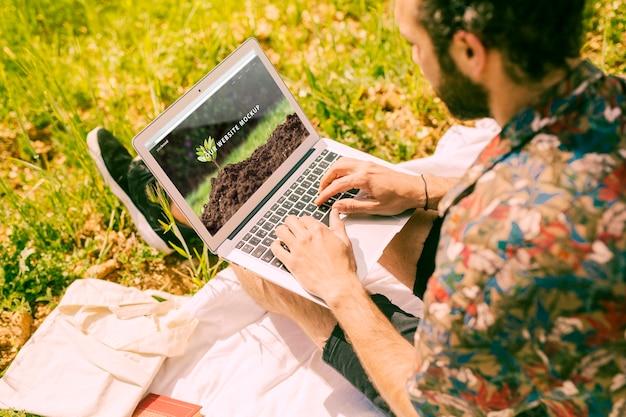 Hombre usando mockup de portátil en la naturaleza
