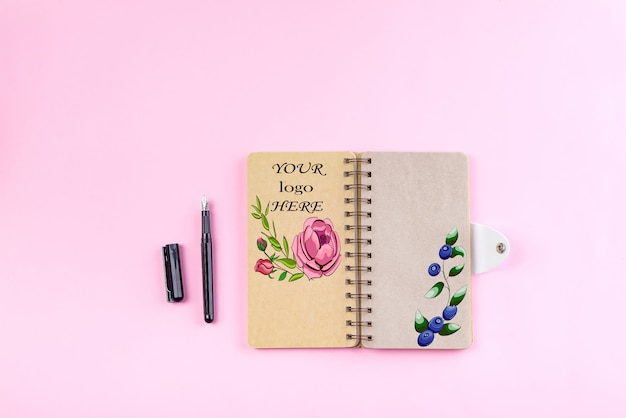 Hoogste mening van spiraalvormig kraftpapier-notitieboekje en witte open pagina die op roze achtergrond wordt geïsoleerd