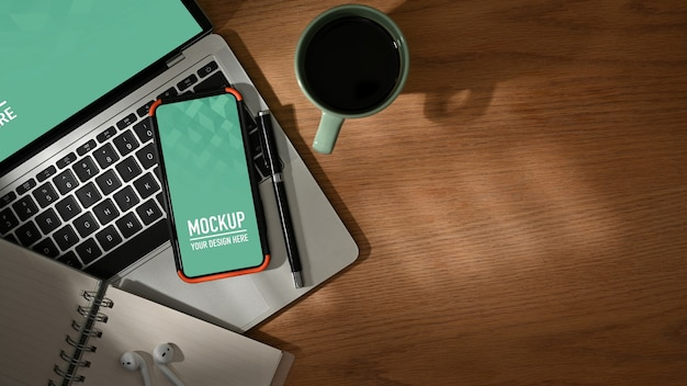 Houten tafel met mockup voor smartphone en laptop, koffiekopje, briefpapier