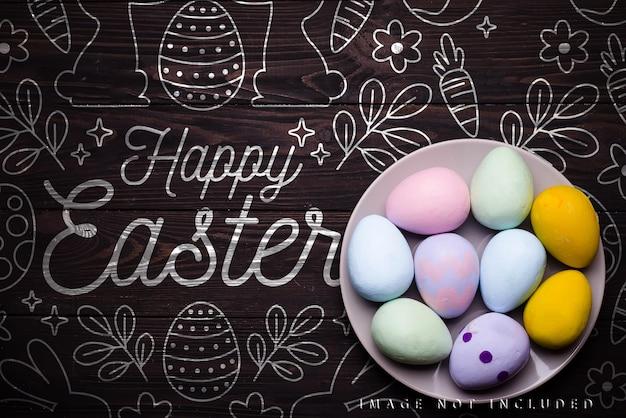 Huevos de colores en placa beige sobre la superficie de la maqueta de madera oscura,