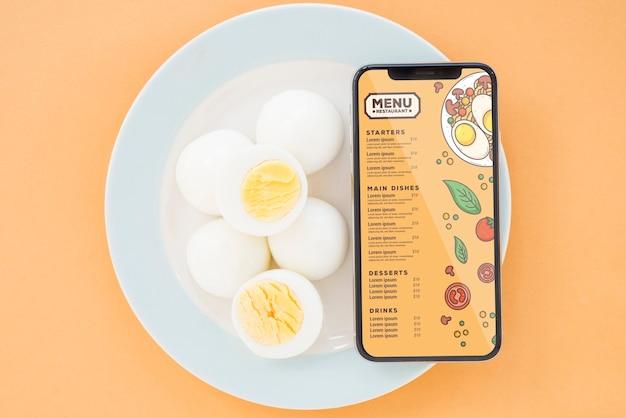 Huevos de primer plano con maqueta de teléfono