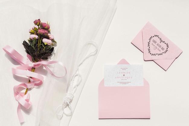 Huwelijksdecoratie in roze tonen met uitnodiging en bloemen