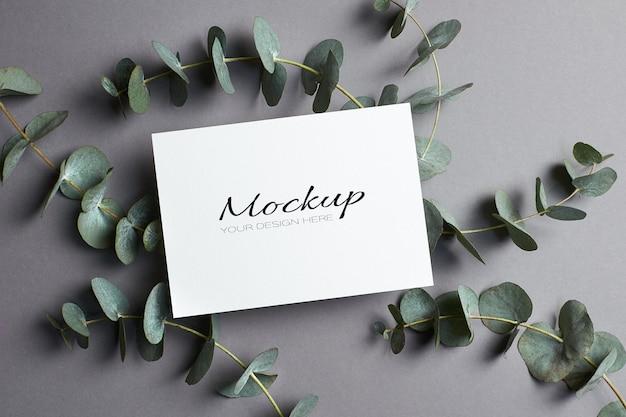 Huwelijksuitnodiging of wenskaartmodel met eucalyptustakjes op grijs