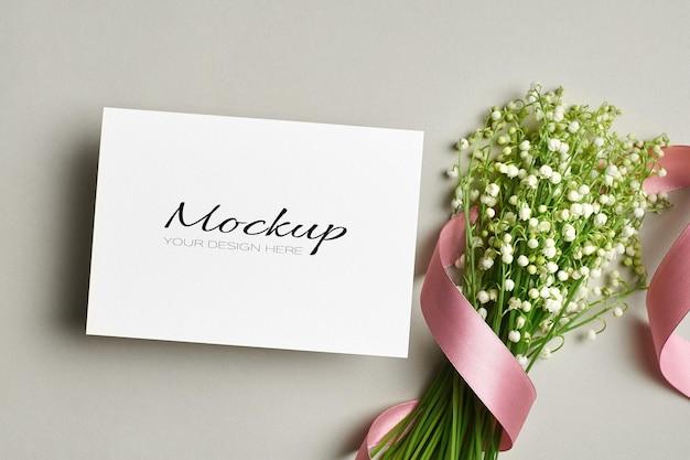 Huwelijksuitnodiging of wenskaartmodel met lelietje-van-dalen bloemenboeket met roze lint