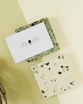 Icono de diseño en tarjeta de nombre blanca en maqueta de cubo de granito