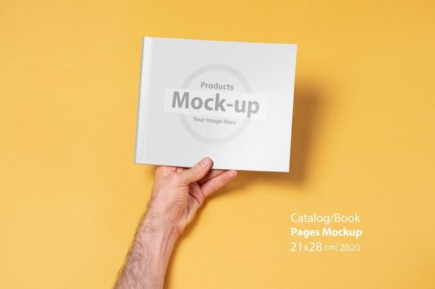 Iemands hand met een catalogus met lege omslag
