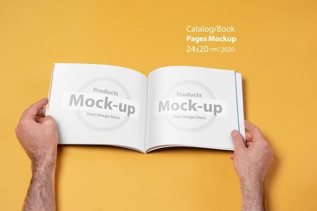 Iemands handen met een geopende catalogus met blanco pagina's