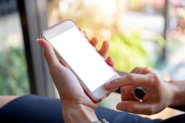 Il fuoco selettivo della mano delle donne facendo uso dello smartphone mobile ha offuscato il fondo