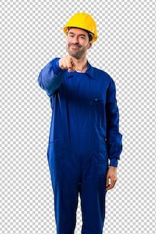 Il giovane operaio con il casco indica il dito voi con un'espressione sicura