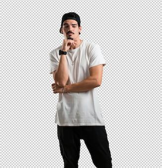 Il giovane rapper che pensa e guarda in alto, confuso su un'idea, cercherebbe di trovare una soluzione