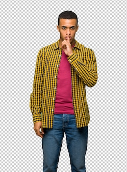 Il giovane uomo afroamericano che mostra un segno del silenzio gesture mettere il dito in bocca
