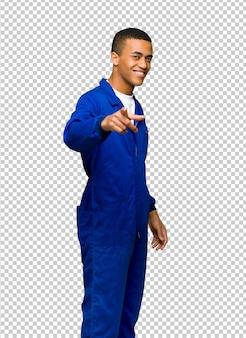 Il giovane uomo afroamericano del lavoratore indica il dito voi con un'espressione sicura