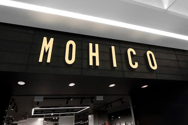 Il modello del logo al neon 3d firma dentro la prospettiva sull'entrata del negozio