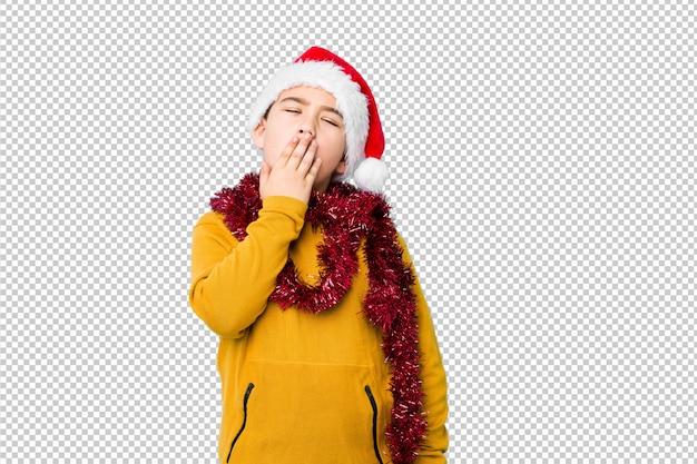 Il ragazzino che celebra il giorno di natale che porta un cappello di santa ha isolato lo sbadiglio mostrando un gesto stanco che copre la bocca di mano.