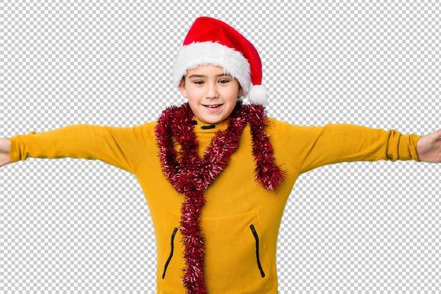 Il ragazzino che celebra il giorno di natale che porta un cappello di santa isolato si sente sicuro dare un abbraccio alla macchina fotografica.