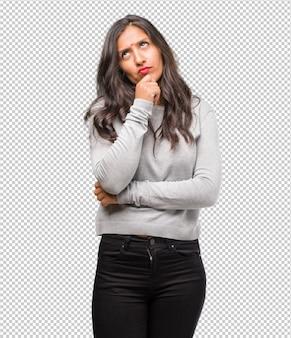 Il ritratto di una giovane donna indiana che pensa e guarda in alto, confuso su un'idea, cercherebbe di trovare una soluzione