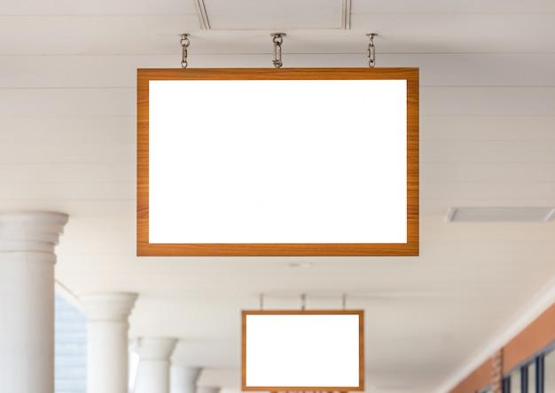 Imagen de la maqueta de la pantalla blanca del marco de madera de la cartelera en blanco fuera del escaparate para la publicidad