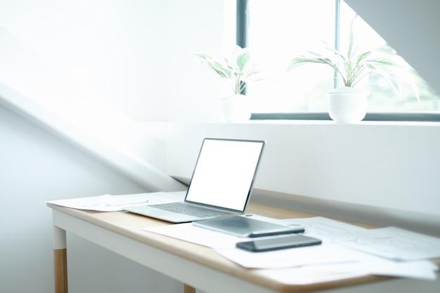 Imagen de la maqueta del portátil en la mesa de madera con el equipo del diseñador gráfico de la aplicación móvil