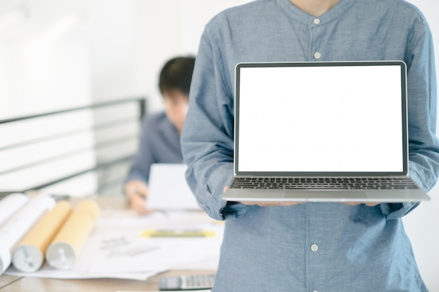 Immagine del modello degli ingegneri che mostrano progetto di costruzione di progettazione del computer portatile in ufficio
