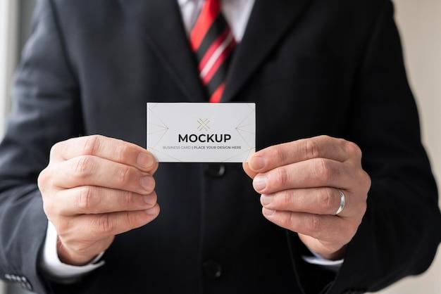 Imprenditore tenendo il biglietto da visita mock-up con entrambe le mani
