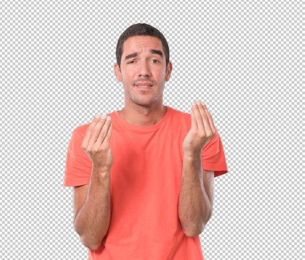 In verwarring gebrachte jonge mens die een italiaans gebaar doet