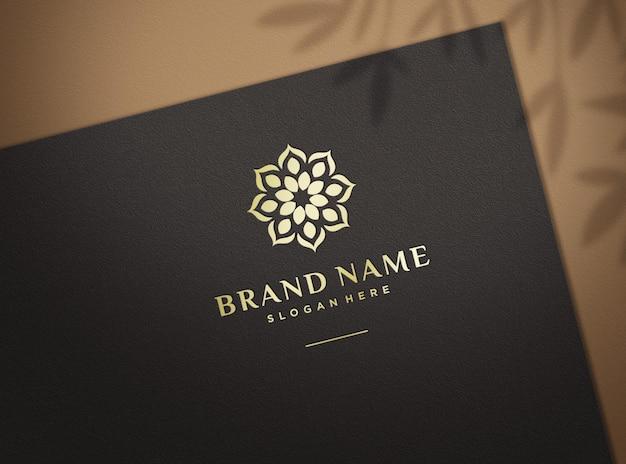 Ingedrukt gouden logo-mockup op zwart papier