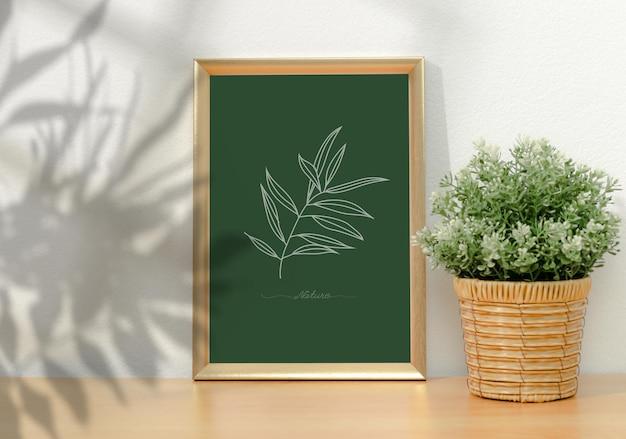 Ingelijst muurkunstmodel in woonkamer en planten in vaas met raamschaduw op witte muur.