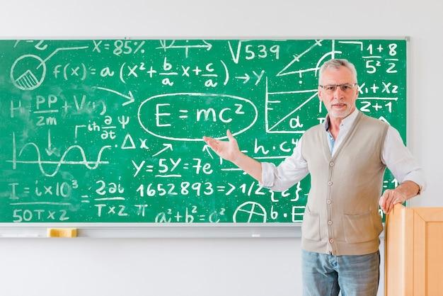 Insegnante che mostra una tavola piena di formule