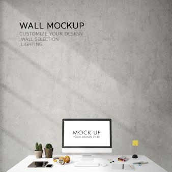 Interior design per lo spazio di lavoro con schermo portatile sul tavolo bianco e parete mockup per carta da parati
