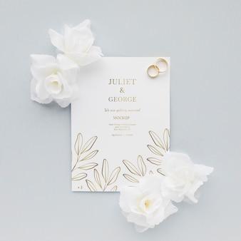 Invitación de boda con flores y anillos.