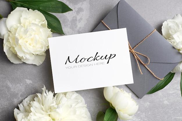 Invitación de boda o maqueta de tarjeta de felicitación con sobre y flores de peonía blanca en gris