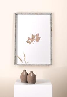 Jarrones con flores y marco en la pared