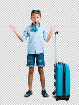 Jong geitje met zonnebril en hoofdtelefoons die met zijn koffer met verrassing reizen