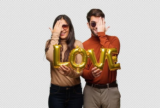 Jong koppel in valentijnsdag schreeuwen blij en die betrekking hebben op gezicht met de hand