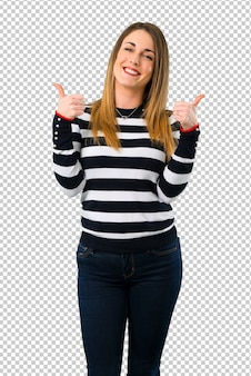 Jong meisje dat van de blonde duimen op gebaar en het glimlachen geeft