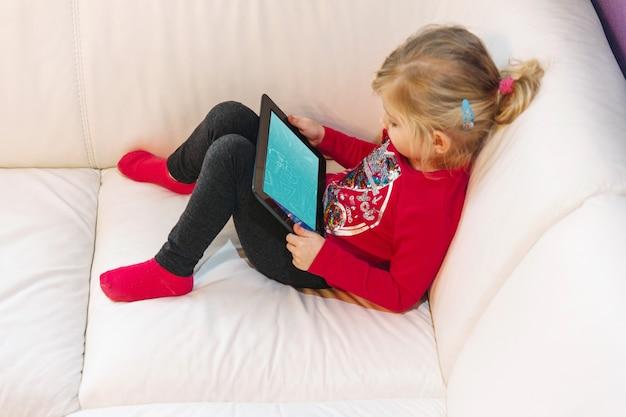 Jong meisje met behulp van de tablet